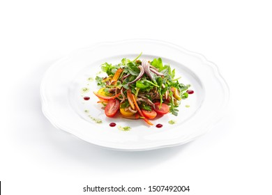 Healthy gourmet salad with sliced beef tongue, arugula, paprika, tomatoes and dressing a la pesto on white plate background. Delicious lunch menu with fresh meat and vegetable salat closeup - Shutterstock ID 1507492004