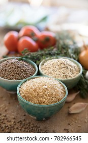 Healthy grains, brown rice, lentils and oats in bowls with veggies in the background.