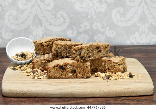 Healthy granola brownies, stacked on a cutting board.