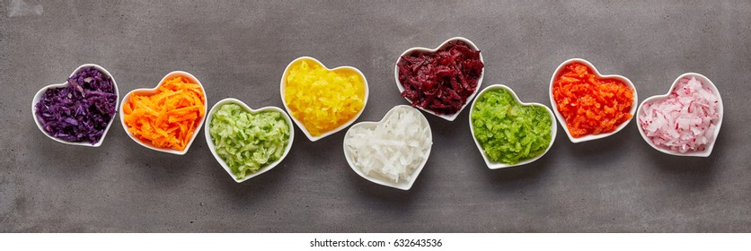 Healthy grated vegetables of different colors in heart-shaped bowls in funny long row as wide banner concept