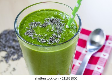 Healthy green fresh fruit and vegetable juice smoothie with green polka dot straw and chia seeds heart garnish