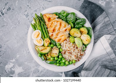 Healthy green grilled vegetables buddha bowl with chicken and quinoa, spinach, egg, zucchini, asparagus, Brussels sprouts and green peas on a gray background. Top view