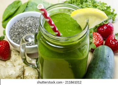 Healthy green juice smoothie surrounded by whole fruits, vegetables and chia seeds with lemon garnish and red polka dot straw