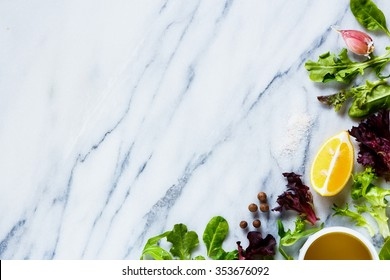 Healthy green lettuce with olive oil, lemon and garlic on marble texture. Background layout with free text space. Bio food, health concept. Top view.