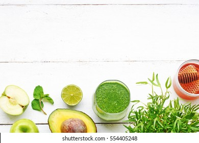 Healthy green meal on a white table. Green breakfast or lunch concept: scrambled eggs with spinach, green smoothie, matcha cake, black coffee, brown sugar, peanut butter toasts, apples. Top view.