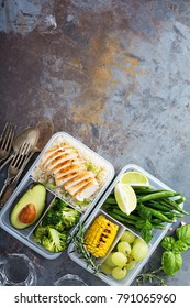 Healthy green meal prep containers with chicken, rice, avocado and vegetables overhead shot with copy space