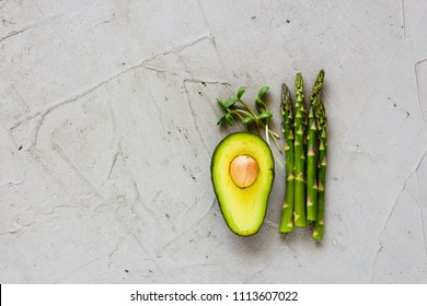 Healthy green raw food clean eating selection flat lay. Avocado, micro greens and aspargus on light background. Cooking ingredients. Top view.