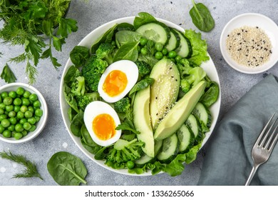 healthy green salad with avocado, eeg, broccoli, cucumber, green peas and spinach in white  bowl, top view
