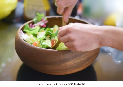 Healthy green salad being tossed in wooden bowl on counter