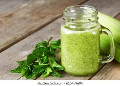 Healthy green smoothie in glass mug on old wooden background