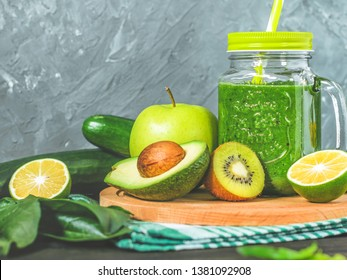 healthy green smoothie with ingredients on a wooden table: apple, kiwi, lime, spinach, mint, avocado, cucumber