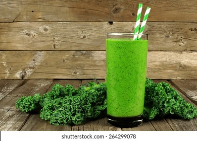 Healthy green smoothie with kale in a glass against a rustic wood background
