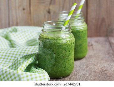 Healthy green smoothie made from spinach, kiwi, bananas and oranges in a jar with green straws on a wooden table, selective focus