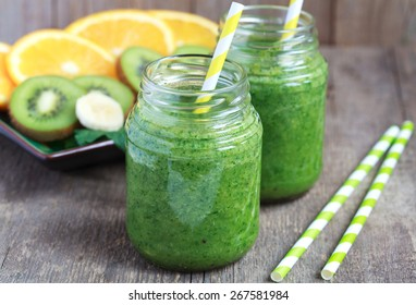 Healthy green smoothie made from spinach, kiwi, bananas and oranges in a jar with yellow straws on a wooden table, selective focus