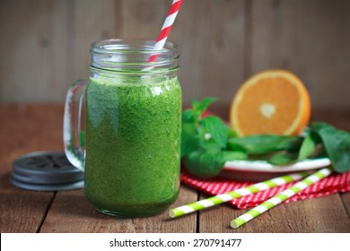 Healthy green smoothie made from spinach, kiwi, bananas and oranges in a jar with red straw on a wooden table, selective focus