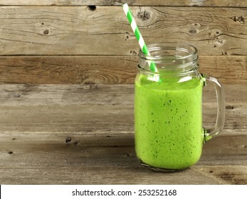 Healthy green smoothie in a mason jar mug on old wood