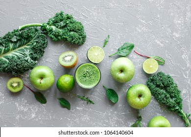 Healthy green smoothie with ripe green fruits, kale and spinach on gray background, top view.