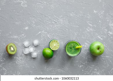 Healthy green smoothie with ripe lime, apple, kiwi and ice cubes on gray background, top view