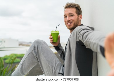Healthy green smoothie selfie sport fitness man taking self portrait picture at gym drinking vegetable juice after workout in sweatpants and sportswear.