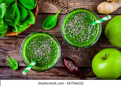 Healthy green smoothie with spinach, apple, ginger and chia seeds on a wooden background. top view