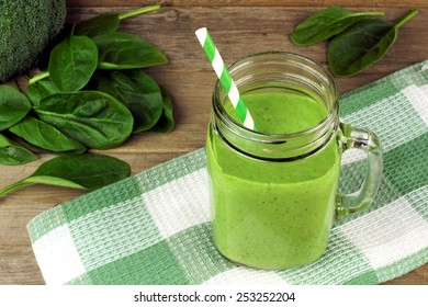 Healthy green smoothie with spinach in a jar mug with checkered cloth against wood