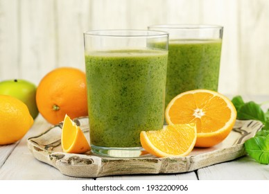 Healthy green smoothie with spinach, mango, orange,lime, apple,citrone in glass jars.