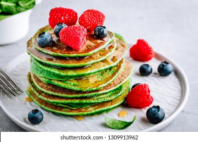 Healthy green spinach pancakes with raspberries, blueberries and honey for breakfast.