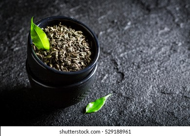 Healthy green tea with teapot and cup on black rock
