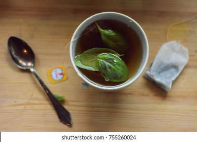 Healthy green tea whit herb in tea cup at wooden light table/ top view