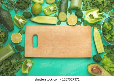 Healthy green vegan cooking ingredients. Flay-lay with wooden daunting and green vegetables and greens, top view. Clean food, vegetarian, detox, diet food.
