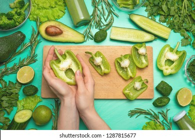 Healthy green vegan cooking ingredients. Flay-lay of female hands cutting green vegetables and greens over a wooden board, top view. Clean food, vegetarian, detox, diet food.