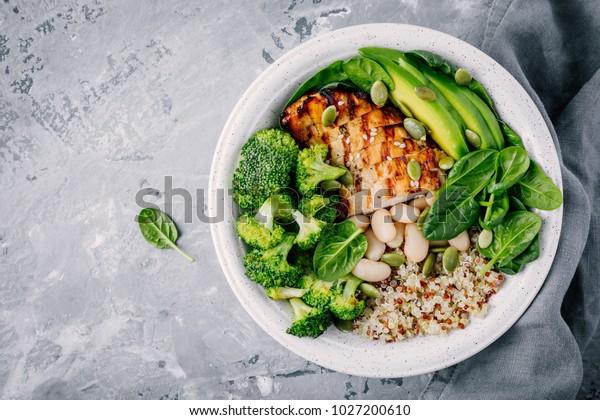 グレイの背景に焼き鳥、キノア、ホウレンソウ、アボカド、ブロッコリー、白豆を使った、健康に良い緑の野菜の仏鉢の昼食。平面図。