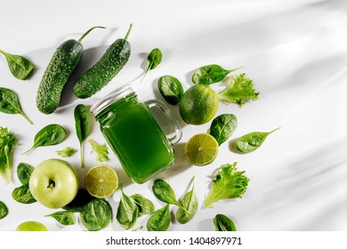 Healthy green vegetable juice with spinach and green fruits and vegetables on white table.