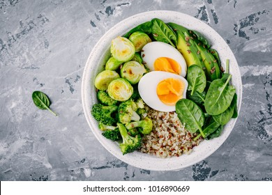 Healthy green vegetarian buddha bowl lunch with eggs, quinoa, spinach, avocado, grilled brussels sprouts and broccoli on dark gray background. Top view.