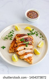 Healthy Grilled Chicken Breast with Fresh Herb and Lemon  Directly Above Vertical  Photo. Cooked Chicken Breast in a White Plate and on White Background..