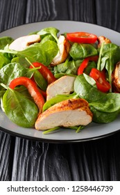 Healthy grilled chicken breast salad with fresh baby spinach and bell peppers closeup on a plate on the table. vertical