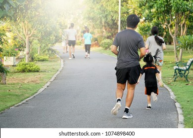 Healthy Group of asian runner jogging in the park.Father and daughter enjoying at sunset in the garden while running on day off. Concept of Relaxation,People,Sport,Healthy,Family.