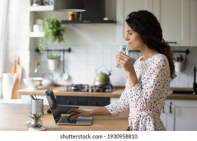 Healthy habit. Relaxed female freelancer working from home start work day from glass of pure crystal water check mail read news on laptop. Happy young woman drink mineral aqua at kitchen by pc screen.
