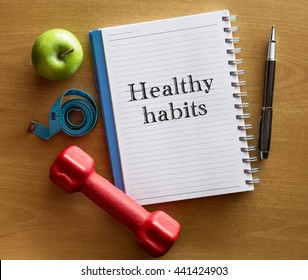 Healthy habits advice or reminder - handwriting on notepad with dumbbell, green apple and measurement tape. Health and fitness concept.