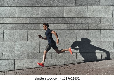 Healthy habits. Full length of young man in sports clothing running while exercising outside