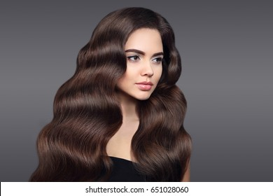 Healthy hair. Beautiful Brunette girl portrait with long shiny wavy hair. Attractive model with curly hairstyle and fresh makeup isolated on studio dark background. Shampoo care product.