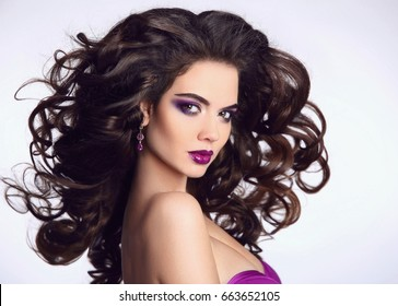 Healthy hair. Beautiful Brunette Girl portrait. Bright makeup. Model Woman advertising long blowing hairstyle isolated on white background. Beauty eyeshadow make up.
