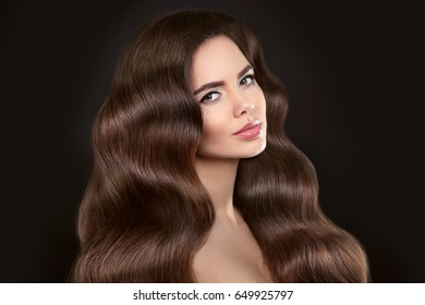 Healthy Hair. Beautiful model girl with shiny brown wavy long hairstyle and makeup isolated on black background. Glossy natural hair. Care and hair products.