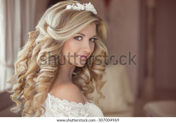 Healthy hair. Beautiful smiling girl bride with long blonde curly hairstyle and bridal makeup. Wedding indoor portrait.
