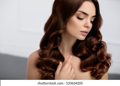 Healthy Hair. Beautiful Woman Model With Long Shiny Wavy Curly Hair Style. Portrait Gorgeous Brunette Girl With Natural Makeup, Beauty Face, Perfect Brown Hair Color And Curls. Cosmetics. High Quality