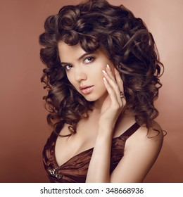 Healthy hair. Beautiful young smiling woman with long curly hairs. Brunette girl model with professional makeup and Manicured nails. beige brown colour.
