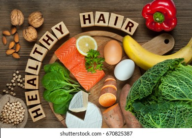 Healthy hair concept. Best foods for healthy hair as salmon, spinach, almonds, sweet potatoes, eggs, walnuts, cabbage, cheese, red pepper, banana and soy.