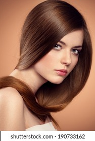 Healthy hair. Hair cosmetics. Studio close-up portrait of pretty young woman with long straight hair looking at camera.