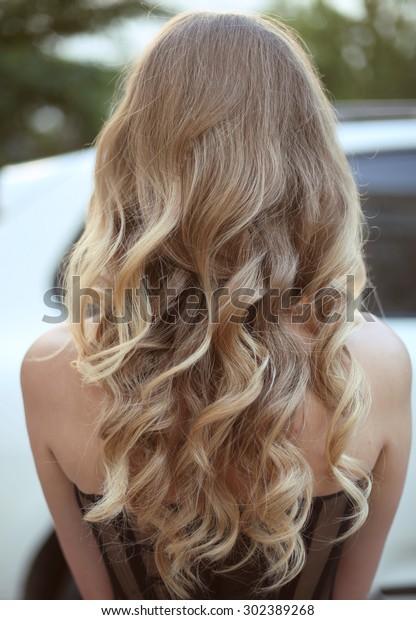 Gezond haar. Krullend lang kapsel. Achteraanzicht van Blond haar. styling.