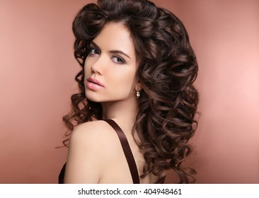 Healthy hair. Makeup. Beautiful brunette woman with long curly hairstyle. Elegant lady with jewelry.